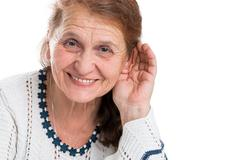 The old woman who rejoices that can hear. Portrait of a happy old woman on a whi Stock Photos