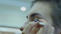 Beautiful girl in a beauty salon does makeup Stock Footage