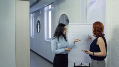 Woman teaches her colleague SMM, SEO in front of board Stock Footage