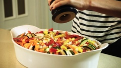 Chopped vegetables laid out in a baking dish and seasoned with black pepper. HD Stock Footage