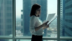 Young businesswoman working with documents standing by window in office Stock Footage