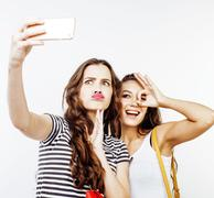 Two best friends teenage girls together having fun, posing emotional on white Kuvituskuvat