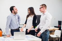 Collaboration is a key to success. Three young business people discussing Stock Photos