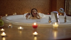 Woman in bath with foam talking on phone and holding bank card and laugh Stock Footage