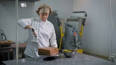 Confectioner with a spatula spread chocolate cream on a freshly baked cake on a Stock Footage