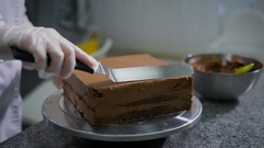 Kitchen in a candy store. The woman in kitchen cooks chocolate cake. The Stock Footage
