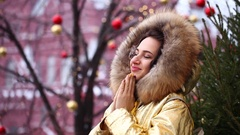 Young happywoman in golden jacket with fur hood poses outdoors in winter Stock Footage