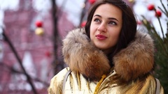 Young beautiful woman in golden jacket with fur hood poses outdoors in winter Stock Footage