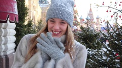Happy girl in a blue knitted hat and gray mink coat, in the street in winter Stock Footage
