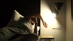 Person turns on light and gets up from bed Stock Footage
