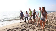 Multiracial group of friends walking at beach Stock Footage
