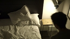 Person lays down in bed preparing to go to sleep Stock Footage