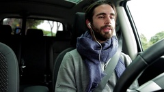 Handsome man in winter driving car talking on cell phone with ear pods Stock Footage