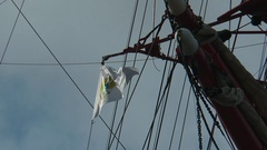 "Triangular flag of the barque ""Sedov"" on the background of blue sky. Stock Footage"