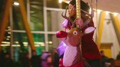 Girl riding Reindeer - Rose Carousel in Winter - Christmas - Butchart Gardens Stock Footage