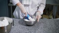 Baker mixes the dough in a metal bowl for the preparation of tasty cookies Stock Footage
