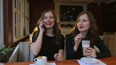 Two beautiful girls drinking coffee in a cafe. Stock Footage