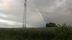 Cloudy sky with rainbow near high voltage electricity pole. 4K Stock Footage