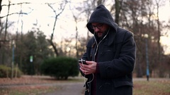 Male man listening to music on cellphone in park Stock Footage