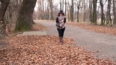 Attractive elegant woman 40 years old with mobile phone in the autumn park going Stock Footage