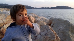 Child on rocks and his chewing-gum, 2 Stock Footage