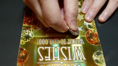 Close up people scratching lottery ticket at home with 4k resolution Stock Footage