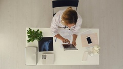 Female doctor using digital tablet to check patient's medical case in medical Stock Footage
