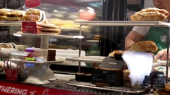 Motion of barista taking food for customer at Starbucks store Stock Footage
