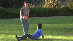 Big brother playing a trick on little brother as he tries to kick a football , s Stock Footage