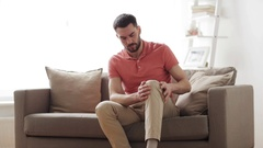 Unhappy man suffering from pain in leg at home Stock Footage