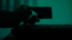 Male hand holding credit card in the darkness over laptop Stock Footage