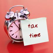 Clock with sticker on it with words Tax Time Stock Photos