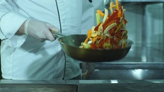 A chef flipping vegetables in a frying pan Stock Footage