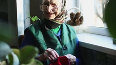 Funny grandmother in glasses sews clothes with a needle. Stock Footage