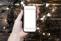Hand holding smartphone on wooden background Stock Photos