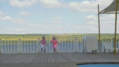 Two little girls running on a pier Stock Footage