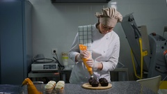 Female pastry gently squeezing white cream milk cream from a food bag for ready Stock Footage