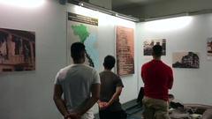 Visitors look at pictures in War Remnants Museum Stock Footage
