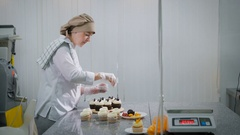 The woman cooks cakes for a holiday. At the girl the order as the candy store is Stock Footage