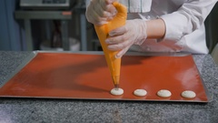 Confectioner with pastry syringe does cookies the same size before baking in the Stock Footage