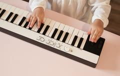 Little girl's hands playing electronic piano Stock Photos