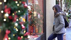 Young woman looks at a window during Christmas shopping Stock Footage
