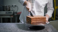 Kitchen. On a table ready chocolate cake. The worker of a candy store in a white Stock Footage