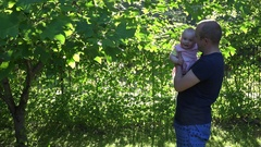 Active daddy with infant daughter have fun in evening sunlight. 4K Stock Footage