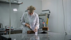Girl in white uniform neatly cuts the chocolate cake into three equal pieces in Stock Footage