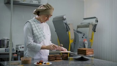 Girl pastry chef dressed in white suit and a brown cap, with a serious look Stock Footage