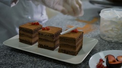 The woman in a candy store. The confectioner in gloves decorates pieces of cake Stock Footage