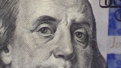 Zoom out $100 dollar bill on top of a pile of more US currency Stock Footage