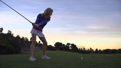 A woman teeing off while playing golf at sunset, super slow motion. Stock Footage