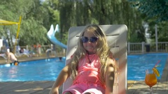 Cute little girl wearing sunglasses lying on a chaise longue on background of Stock Footage